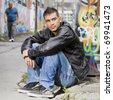 adult handsome man posing outdoors in a graffiti wall background - stock photo