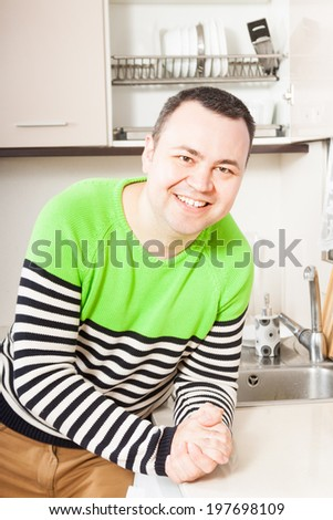 Adult happy man at domestic kitchen - stock photo