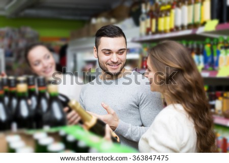 Adult happy shoppers choosing bottle of wine at liquor store