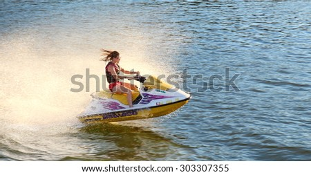 Adult having fun jumping a wave riding yellow and white jet ski in California Ocean