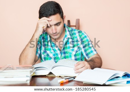 Adult hispanic man studying with a pile of books on his desk - stock photo