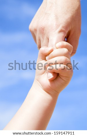 Adult holding a child by the hand against a cloudy blue sky - stock photo