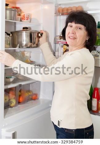 Adult housewife standing at   kitchen near   refrigerator.  - stock photo