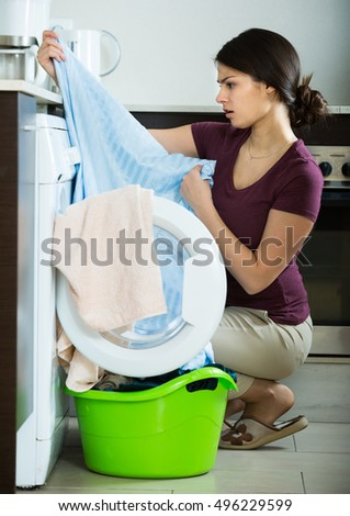 Adult housewife with musty towels after laundry at home