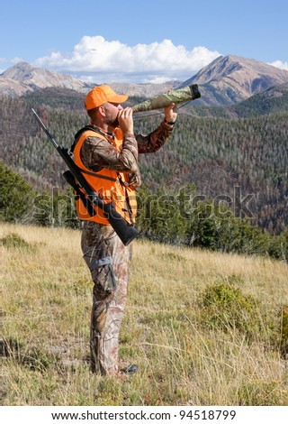 adult hunter blowing an elk call - stock photo