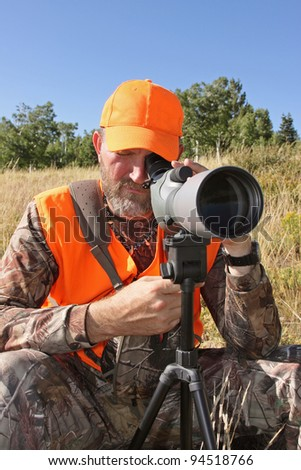 adult hunter looking through spotting closeup - stock photo