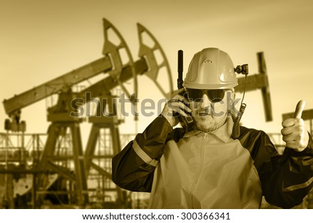 Adult industrial worker in glasses, with helmet camera, talking on radio transceiver, on a  oil field background. Toned sepia.