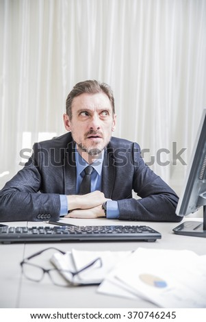 adult male businessman sitting behind a Desk looked up in surprise