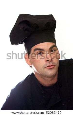 adult male chef in black uniform looking directly at viewer