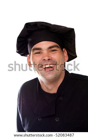 adult male chef in black uniform looking directly at viewer and laughing