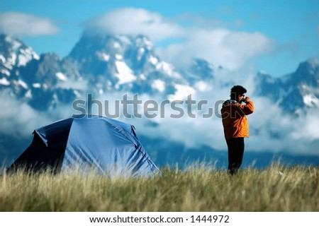 adult male drinking coffee next to his tent - stock photo