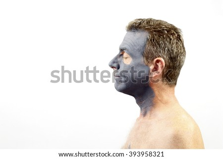 Adult male in his forties facing left wearing a dark gray charcoal and bentonite mud mask. A guy with a charcoal and bentonite mud mask skin treatment on his face