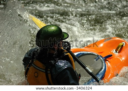 adult male in orange kayak,green helmut paddling out of tight river rapid in dowd chute near vail colorado