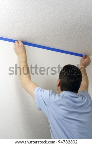 Adult male pressing blue painter's tape onto a white wall below a ceiling in order to protect the wall when he paints the ceiling above.