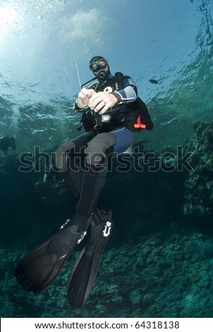 Adult male scuba diver holding a surface marker buoy and hovering mid-water. Yolanda reef, Ras Mohamed National Park, Red Sea, Egypt. - stock photo