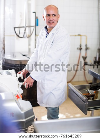 Adult male standing in production workshop in white overalls