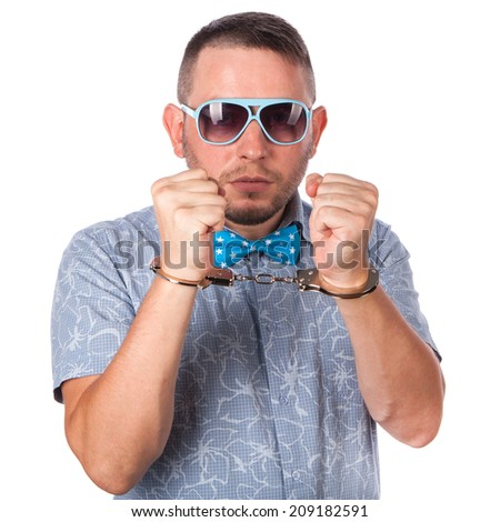 Adult male with beard in a blue bow tie in summer shirt in police handcuffs isolated on a white background - stock photo
