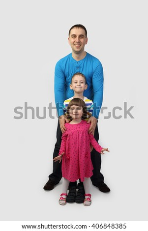 Adult male with little children full height portrait on gray background - father, son and daughter - family relations and happiness concept - stock photo
