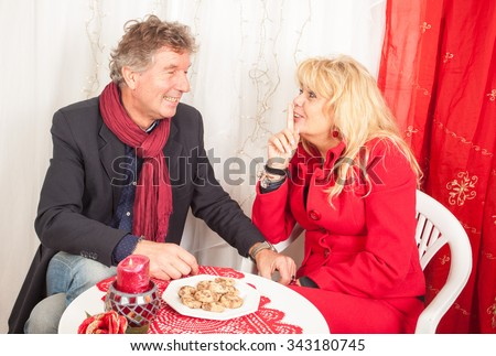 Adult man and woman in an elegant setting with Christmas decorations.