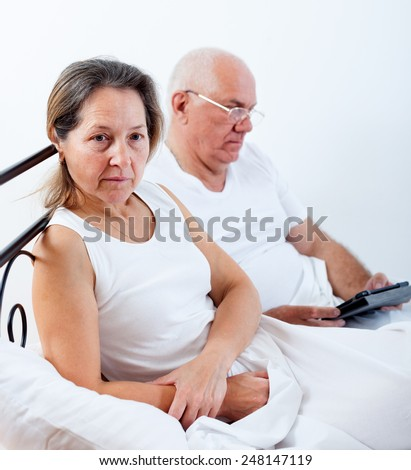 Adult man arguing with   woman sitting in bed. - stock photo