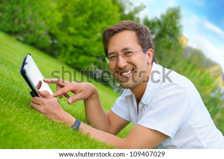 Adult man at summer park resting on weekend using his tablet computer to communicate friends or have fun with new photo, video and audio - stock photo