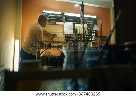 Adult man at work as artist, chiselling a bas-relief in his atelier. He works with hammer and ceasel on a wood painting.  - stock photo