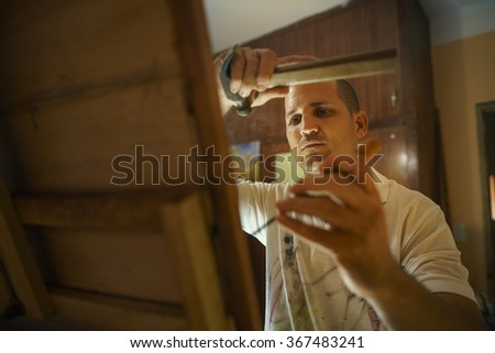 Adult man at work as artist, chiselling a bas-relief in his atelier. He works with hammer and ceasel on a wood painting.