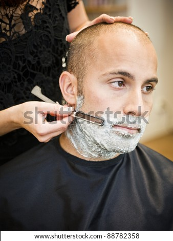 Adult man being shaved at the hair salon - stock photo