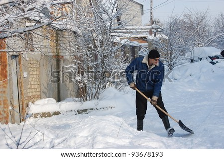 Adult man clean owns road to home against snow.Near Kiev,Ukraine - stock photo