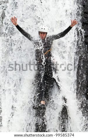 ADULT MAN DESCENDING INTO A WATERFALL SHOOT FROM THE WATER LEVEL