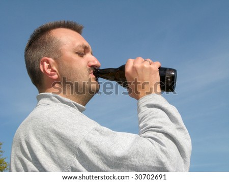 Adult man drinking from the bottle neck