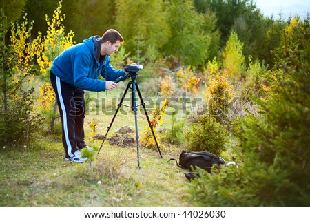Adult man filming with the camcorder on a tripod outdoors - stock photo
