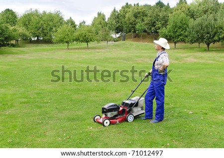 Adult man (gardener) in the blue overalls and straw hat with the lawn mower on a large lot - stock photo