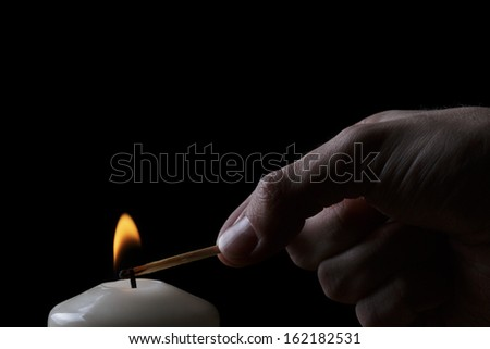 adult man hand set fire a candle, black background