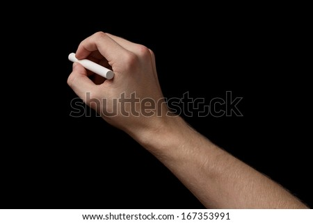 adult man hand with chalk to write something, isolated on black - stock photo