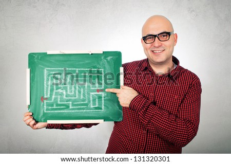 Adult man holding green chalkboard with labyrinth showing the right way