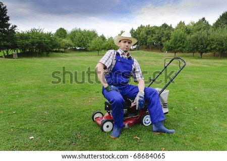 Adult man in blue (gardener), rubber boots and straw hat standing on a large park-like grounds, leaning proudly on his gas lawn mower. - stock photo