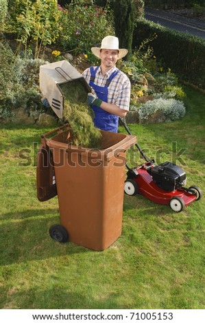 Adult man in blue overalls in the garden and filled grass clippings in the trash, in the background stands a lawnmower