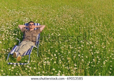 Adult man in casual clothing sitting in a deck chair on a flowery meadow and a rest - stock photo