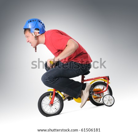 Adult man in helmet goes on a children's bicycle - stock photo