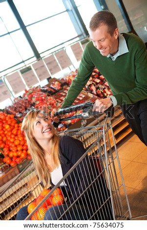 Adult man in playful mood pushing shopping cart while woman sitting in it - stock photo