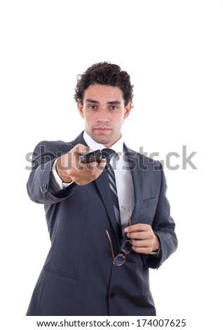 Adult man in suit holding glasses and changing channel with remote - stock photo