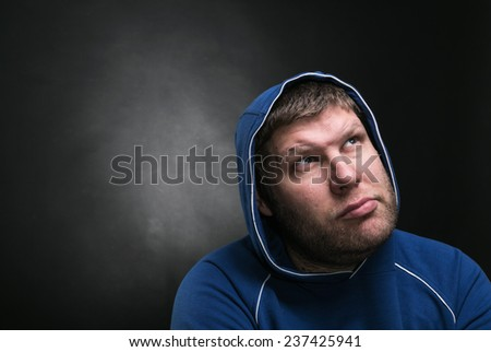 Adult man in the hood sits thinking - stock photo