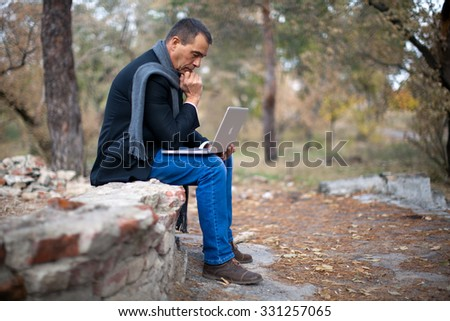 Adult man in the park. Wearing a black suit, jeans and grey scarf. Working on laptop. Thinking
