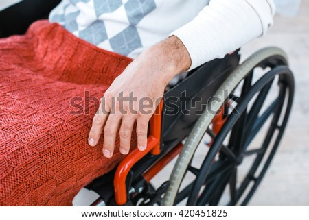 Adult man in wheelchair. Close up photo of man sitting in wheelchair - stock photo