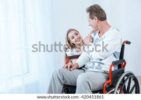 Adult man in wheelchair. White interior with big window. Man and young helper smiling - stock photo