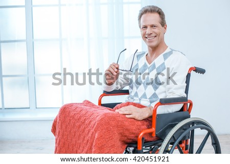 Adult man in wheelchair. White interior with big window. Man smiling, holding glasses and looking at camera - stock photo