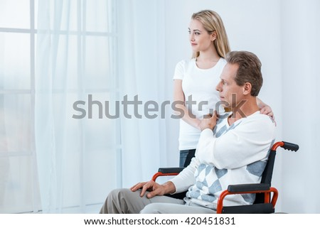 Adult man in wheelchair. White interior with big window. Sad man looking at window. Young helper is near him - stock photo