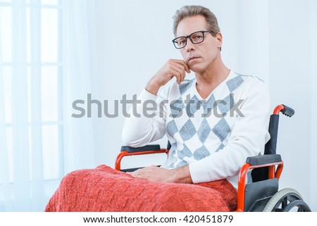 Adult man in wheelchair. White interior with big window. Sad man with glasses looking at camera - stock photo