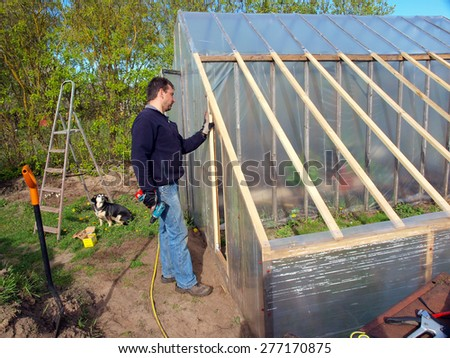 Adult man is building plastic film covered small greenhouse   - stock photo